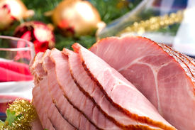 stock photo of christmas dinner  - Holiday table setting with delicious whole baked sliced ham vegetable salad and glasses of red wine - JPG
