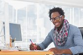 Smiling designer drawing with a red pencil on a desk in a modern office