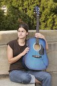 stock photo of acoustic guitar  - one young brunette woman holding a blue guitar looking thoughtful - JPG