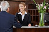 Smiling female receptionist greeting a senior guest with handshake