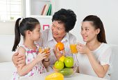 Asian family drinking orange juice. Happy Asian grandparent, parent and grandchild enjoying cup of f