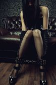 stock photo of gothic  - Sexy gothic girl with legs in leg cuffs - JPG