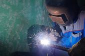 stock photo of pipe-welding  - Welder in protective suit and mask welds metal pipes - JPG