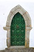 stock photo of ironworker  - Green medieval wooden door with ornate ironwork that goes to a point at the top on a white washed wall - JPG