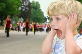 pic of school carnival  - A cute toddler boy covers his ears as he watches a school marching band walk by in a parade - JPG