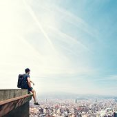 pic of parkour  - Young man sitting on a roof and looking city - JPG
