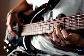 picture of string instrument  - Close up photo playing five string bass guitar