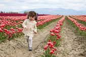 picture of mary jane  - A little girl with dirty knees running in a tulip field - JPG