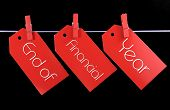 foto of year end sale  - End of Financial Year red ticket sale tags hanging from pegs on a line against a black background - JPG