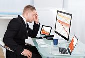 picture of financial audit  - Despairing businessman faced with financial losses sitting at his desk consulting three graphs on different monitors all dropping into the red - JPG