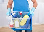 pic of tub  - Janitor or cleaner wearing an apron and gloves carrying a tub of cleaning supplies as he goes about his work at the office - JPG