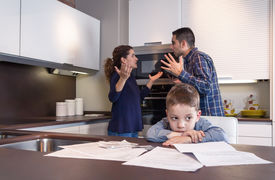 stock photo of suffering  - Sad child suffering and his parents having hard discussion in a home kitchen by couple difficulties - JPG