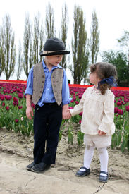 picture of mary jane  - An adorable buy and girl holding hands among tulips - JPG