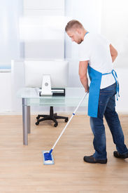 picture of disinfection  - Handsome male janitor or cleaner cleaning the floor in an office building using a mop to wash the and disinfect the surface - JPG