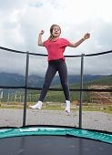 stock photo of 11 year old  - 12 year old teenage girl jumping on a trampoline in the Andorra Pyrenees Mountains - JPG