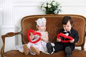 picture of little black dress  - Little beautiful lady in white long dress and boy in black suit sitting on couch with hearts - JPG