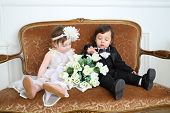 picture of fiance  - Beautiful little kids in costumes bride and groom sitting on couch with bouquet of flowers - JPG