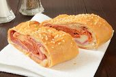 stock photo of bread rolls  - Italian bread roll sandwich with pastrami cheeses and salami - JPG