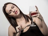 image of alcohol abuse  - Young woman with a glass of wine and handcuffs - JPG