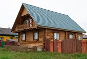 foto of log fence  - Beautiful country log house with a green roof - JPG