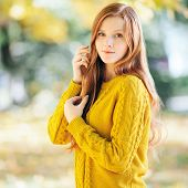 stock photo of redhead  - Autumn portrait of a young cute redhead woman in yellow sweater - JPG