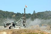 foto of shale  - Rock drill working a site in preparation for a blasting operation in shale rock - JPG