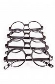 picture of bifocals  - Stack of black glasses isolated on white - JPG