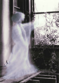 stock photo of banshee  - A glowing ghostly prescence points through the window of an old ruined mansion.                    - JPG