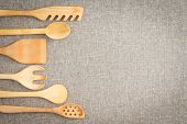 stock photo of food preparation tools equipment  - Wooden cooking utensils for food preparation arranged in a curving row as a decorative side border on a neutral beige linen textile with copyspace - JPG