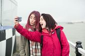 stock photo of memento  - Two playful young women posing for a selfie on a walkway laughing and pulling faces at the camera on their mobile phone - JPG