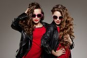 stock photo of sisters  - Sisters twins in hipster sun glasses laughing Two fashion models Women smiling positive Friends group having fun - JPG