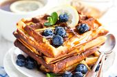 stock photo of berries  - Lemon blueberry waffles with honey zest fresh berries and cup of tea - JPG
