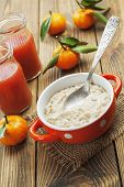 pic of porridge  - Porridge in an orange bowl juice and mandarins on the table - JPG