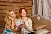 foto of sisters  - Two sisters a blonde and a redhead listening to music on headphones - JPG