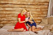 pic of sisters  - Two sisters blonde listening to music on headphones - JPG