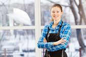 image of apron  - Young woman hairdresser in apron standing near window - JPG