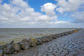 image of dike  - Storm raging over a lake along a dike through Flevoland in spring - JPG