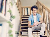 stock photo of breather  - Man sitting with a mug on the stairs - JPG