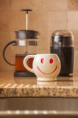 stock photo of taupe  - Brewing a cup of coffee with bean grinder and french press for smile face mug - JPG