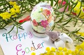 stock photo of decoupage  - Hand painted decoupage Easter egg on woodensurface with a Happy Easter card and two toy rabbit - JPG