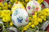 stock photo of decoupage  - hand painted decoupage Easter egg in a basket full of yellow flowers and two yellow chickens - JPG