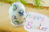 stock photo of decoupage  - Hand painted decoupage Easter egg on a wooden board with a Happy Easter card - JPG