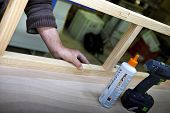 stock photo of carpentry  - Man working a wooden piece in a carpentry workshop - JPG