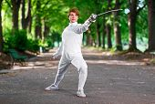 pic of rapier  - Young beautiful rapier fencer woman staying in park alley ready for competition - JPG