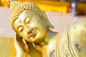 stock photo of recliner  - reclining golden buddha statue in buddhist asian temple - JPG