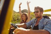 stock photo of buggy  - Happy couple enjoying on a long drive in a car. Friends going on road trip on summer day. Caucasian young man driving a car and joyful woman with her arms raised.
