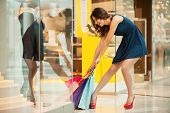 picture of heavy bag  - Full length of tired young woman in blue dress trying to pick up the heavy shopping bags - JPG