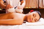 stock photo of therapist massage  - Attractive young woman lying on front while massage therapist massaging her back - JPG