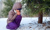 foto of winter trees  - Sad little girl in winter clothes is sitting near a fir-tree in the winter forest and endeavouring to warm up her cold hands ** Note: Shallow depth of field - JPG