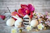 image of figurine  - Small White Rabbit Figurine with Easter Eggs Surrounded by Bright Pink Orchids and Blossoms with Rustic Wooden Background - JPG